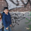 Stock Photo: Young children hanging out near a grungy wall