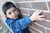 Young child hanging out near a grungy wall — Stock Photo