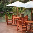House patio with table and chairs under umbrella - Stock Photo