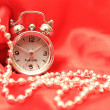 Hours and beads on a white red satiny ba — Stock Photo #2734204