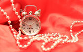 Hours and beads on a white red satiny ba — Stock Photo