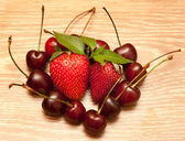 Heart from a sweet cherry and a strawberry — Stockfoto