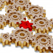 Some golden gears with one red — Stock Photo