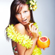 Beautiful girl drinking grapefruit - Stock Photo