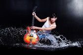 Rock-n-roll girl playing a guitar in water on black — Stock Photo