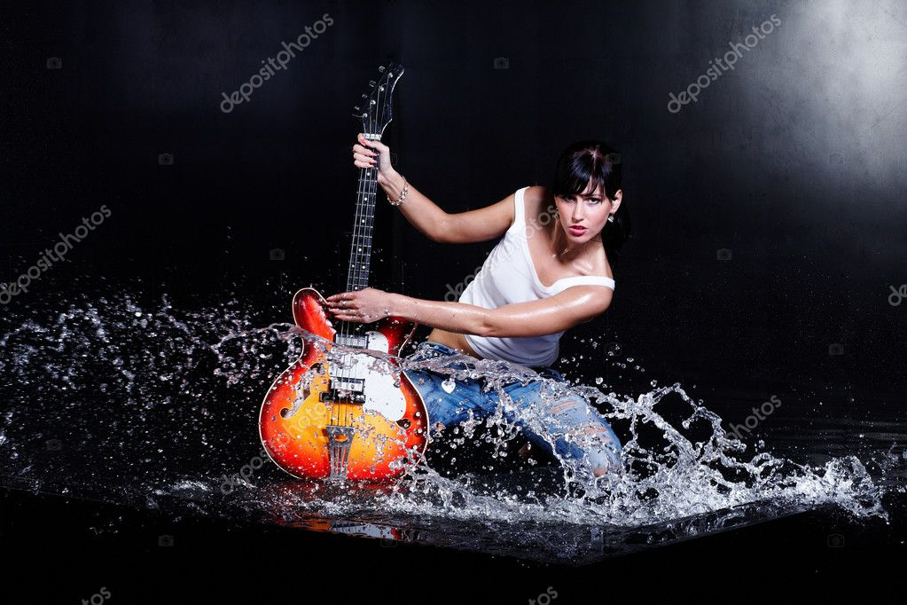 Rock-n-roll girl playing a guitar in water on black  Stock Photo #3826151