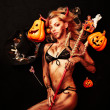 Beautiful devil with trident and Halloween accessories on black — Stockfoto