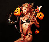 Beautiful devil with trident and Halloween accessories on black — Stock Photo