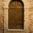 Stockfoto: Wooden door in stone archway
