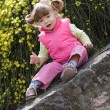A little girl sitting on old stone wall — Stock Photo
