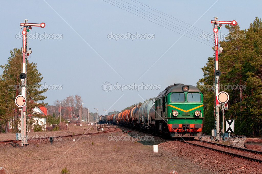 Freight train hauled by two diesel locomotives leaving the station in the middle of the woods  Stock Photo #2994637
