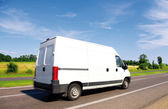 White delivery mini truck on highway over blue sky. — Stock Photo