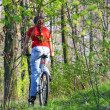 Girl biking in forest — Stock Photo