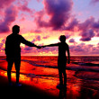 Silhouetted loving couple at sunset - Stock Photo