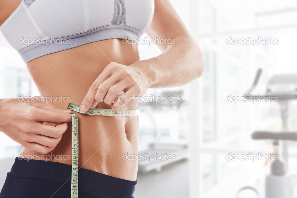 Close up view of young beautiful woman measuring her waist — Stock Photo #2764539