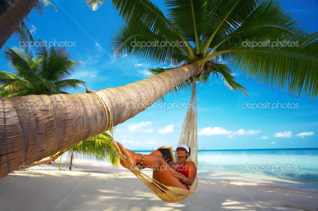 View of nice woman reading a book in hammock in tropical environment  Stock Photo #2900880