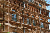 Scaffolds round an old brick building — Stock Photo