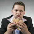 Disapointed businessman eating burger — Stock Photo