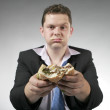 Unhappy businessman holding a hamburger — Stock Photo