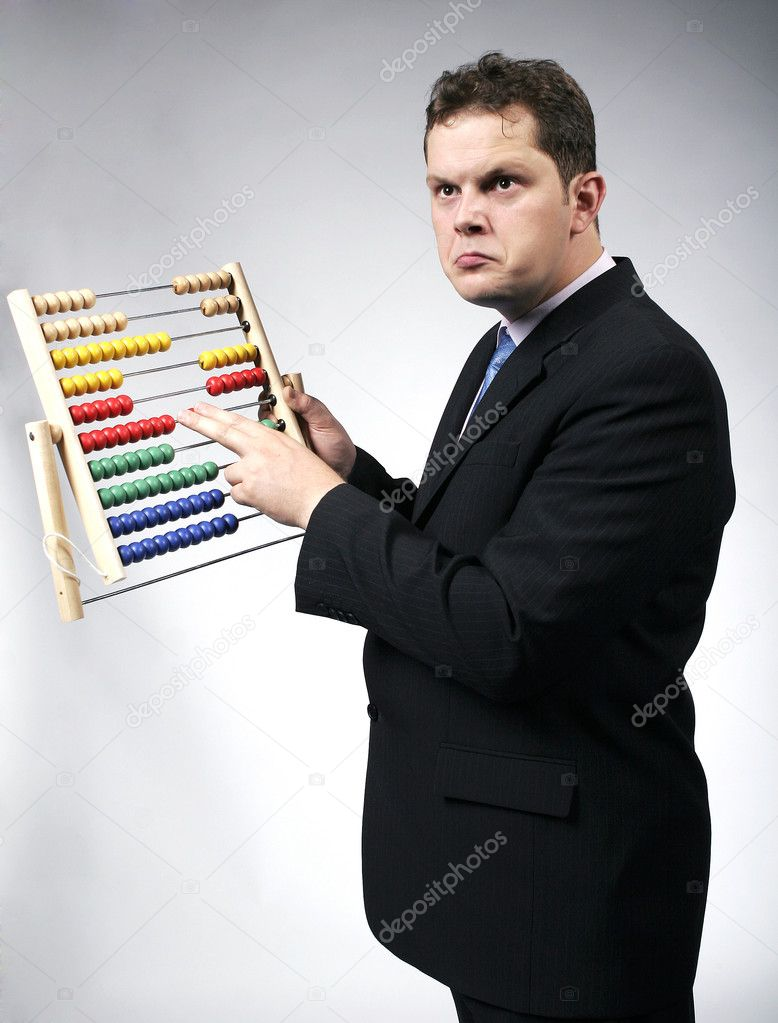 Confused businessman calculating with a multicolor abacus. Studio shot. — Stock Photo #2829081
