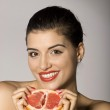 Smiling woman with a grapefruit slice — Stock Photo