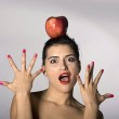 Woman holding an apple on her head — Stock Photo