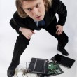 Funny portrait of a businessman with broken laptop - Stock Photo