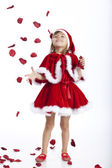 Happy little Santa girl and flying rose petals — Stock Photo