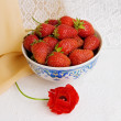 Stock Photo: Dishes with strawberries and a flower