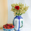 Strawberries and a vase with flowers — Stock Photo
