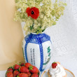 Stock Photo: Strawberries, cake and a vase with flowers