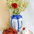 Strawberries, cake and a vase with flowers — Stock Photo