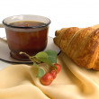 Brown glass cup with tea and croissants — Stock Photo