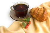 Brown cup of tea and croissants — Stock Photo
