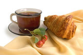 Brown glass cup with tea and croissants — Photo
