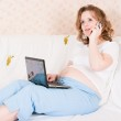 The pregnant woman with the laptop and a mobile phone on a sofa — Stock Photo