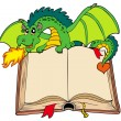 Stock Vector: Green dragon holding old book