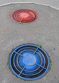 Red, blue street cover, sewerpipe — Stock Photo