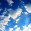 White clouds on blue sky, sun rays, weather — Stock Photo