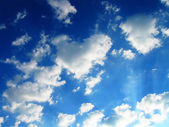 White clouds on blue sky, sun rays, weather — Stockfoto