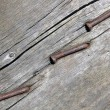 Rusty nail on dry vintage wood surface - Stock Photo