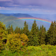Rainbow in mountains - Stock Photo