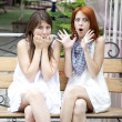 Two girls gossiping on bench at garden. — Stock Photo