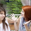 Stock Photo: Two girls gossiping on bench at garden.