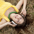 Young beautiful girl in yellow with headphones at field. — Stock Photo #3464007
