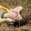 Young beautiful girl in yellow with headphones at field. — Stock Photo #3464028