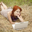 Young fashion girl with notebook lying at field — Stock Photo