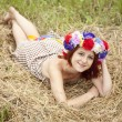 Stock Photo: Girl in Slav national wreath lying at field.