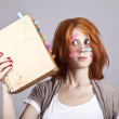 Red-haired businesswoman with book and notes on face. — Stock Photo #3464752