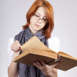 Young doubting fashion girl in glasses with old book — Stockfoto